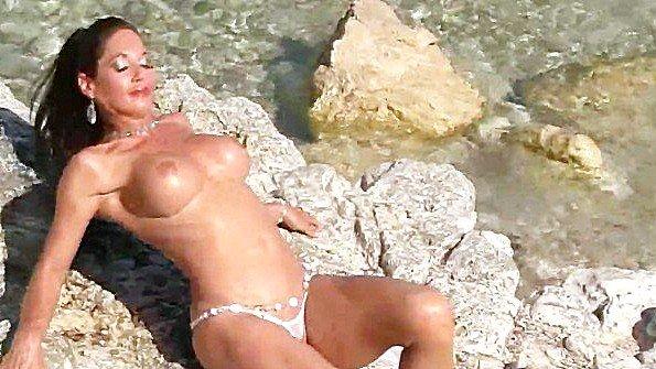 Домохозяйка с крупными дойками нежится обнаженная на берегу моря