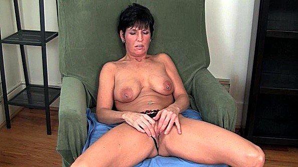 Баба с пирсингом в самом соку ласкает дыру своими пальцами в кресле