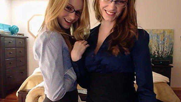 Две очкастые красотки пикантно раздеваются на камеру и обещают секс