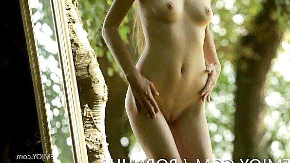 Обнаженная девушка смотрится на себя в зеркало в лесу и радуется