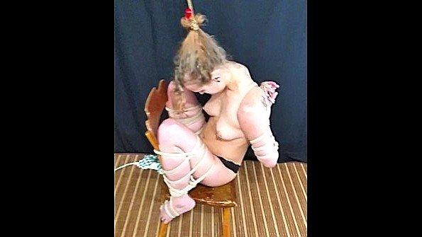 Грубо связанная рабыня сидит на стуле и терпит стимуляцию
