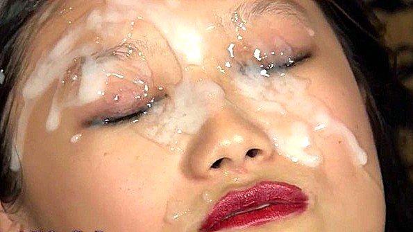 Азиатка покорно лежит и подставляет лицо под льющуюся сперму