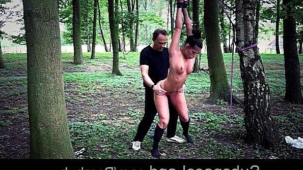 Хозяин привязывает рабыню к дереву в лесу и заставляет сосать хуй