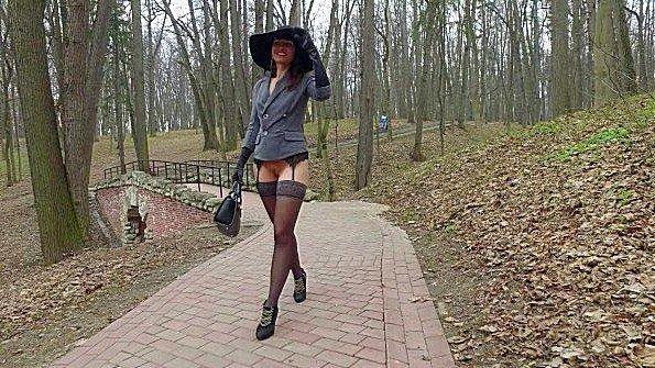 Бабенка гуляет по парку с обнаженной пиздой в чулках и радуется