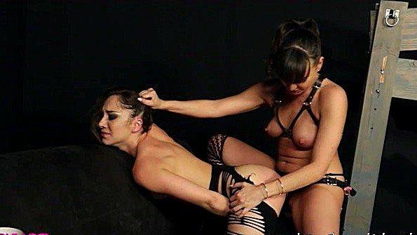 Трахает скованную рабыню страпоном и слушает ее бурные вопли