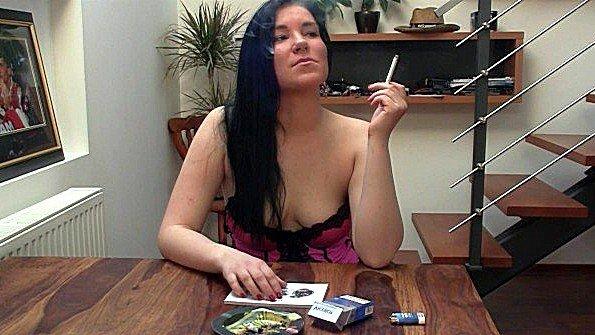 Девица с большими грудями курит сигарету за столом и ласкает дойки